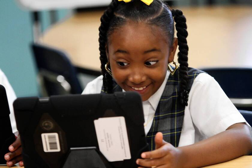 Beautiful Morris smiles as she explores her new iPad. Although L.A. Unified originally said keyboards weren't essential, new state tests can't be taken on iPads without them.