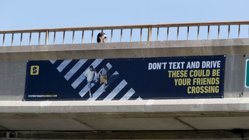 A safety banner warns drivers to not text and drive, as seen on the bridge over Verdugo Road at Glen