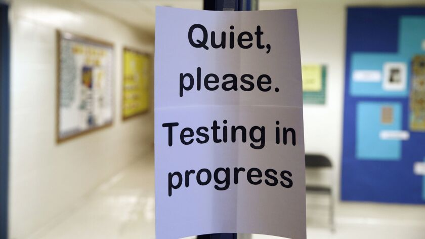 FILE - In this Jan. 17, 2016 file photo, a sign is seen at the entrance to a hall for a college test