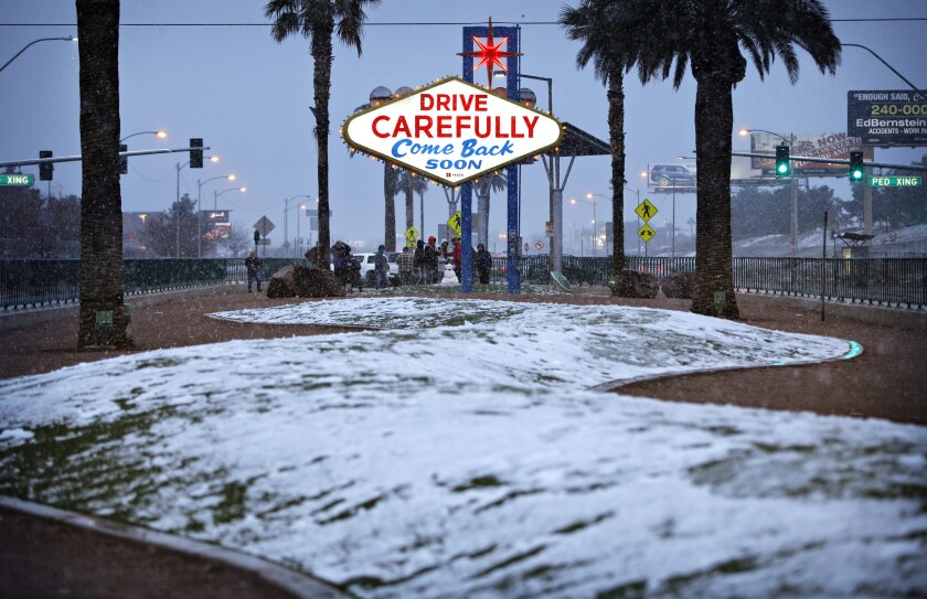 "Snow accumulates on a median along the Las Vegas Strip at the ""Welcome to Fabulous Las Vegas"" sign,"