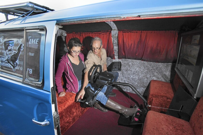 Ben Bennani, owner of A&A Car Rental in Costa Mesa, presses on a lever as student driver Hayley McClements, 17, of Fountain Valley steps on a pedal in a driving simulator inside a 1969 Volkswagen bus.