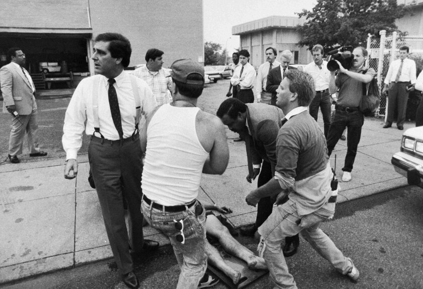 FILE - In this Sept. 14, 1989, file photo, Mayor Jerry Abramson, left, checks on one of the victims of the shooting spree at the Standard Gravure printing plant in downtown Louisville, Ky. Eight were killed and 12 injured by fellow employee Joseph Wesbecker, who also turned the gun on himself. (Gar