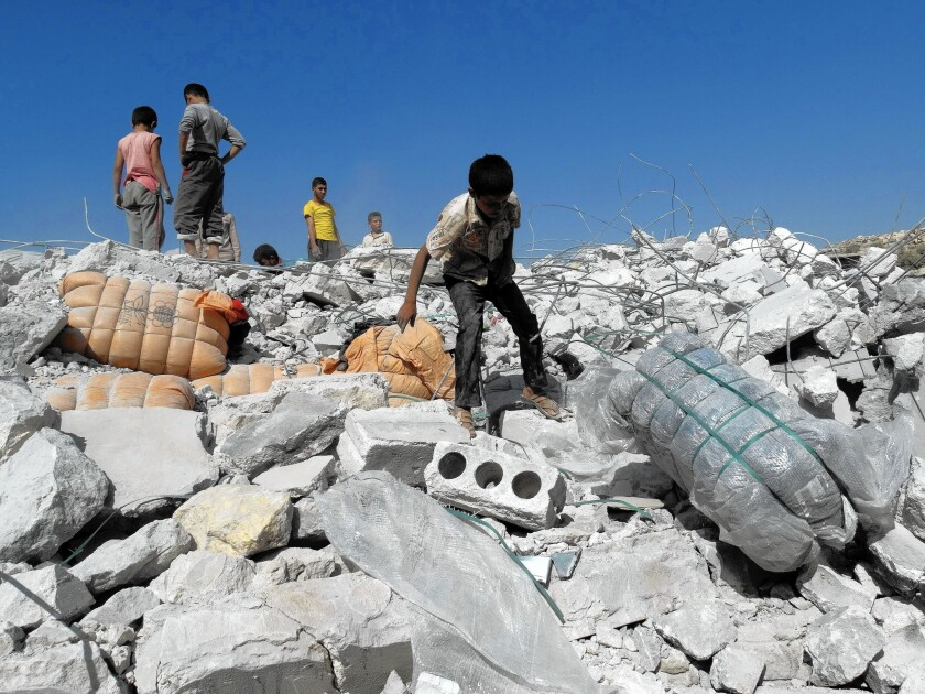 Syrians inspect the rubble of a home reportedly hit by a U.S.-led coalition airstrike in Kafar Daryan. As many as two dozen civilian deaths in airstrikes were reported by Syrians.