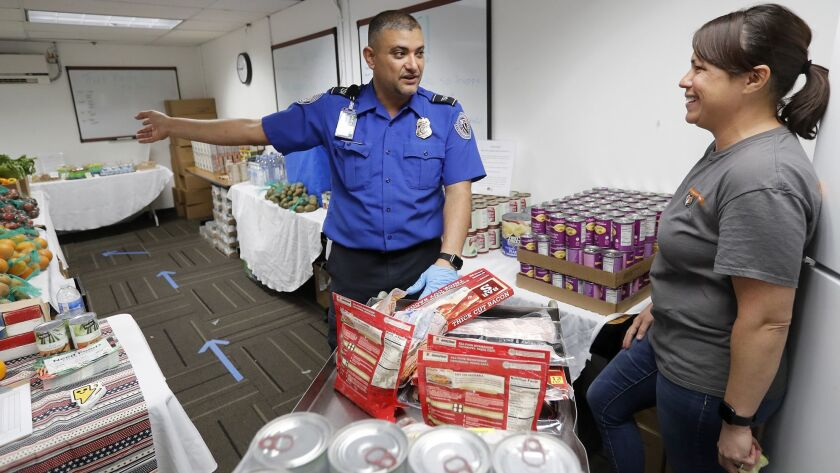 TSA worker Steve Rivera, center, talks to Joylani Kamalu, right, Second Harvest Food Bank Orange Cou