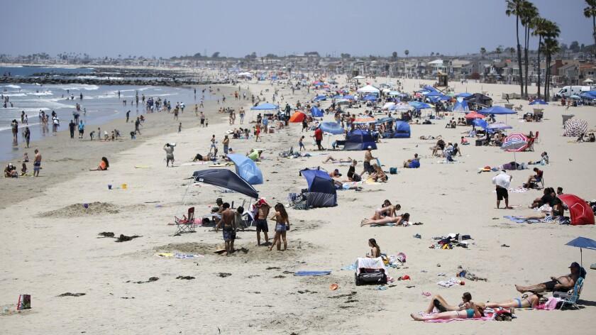 Beachgoers practice social distancing near the Newport Pier in Newport Beach in May 2020.