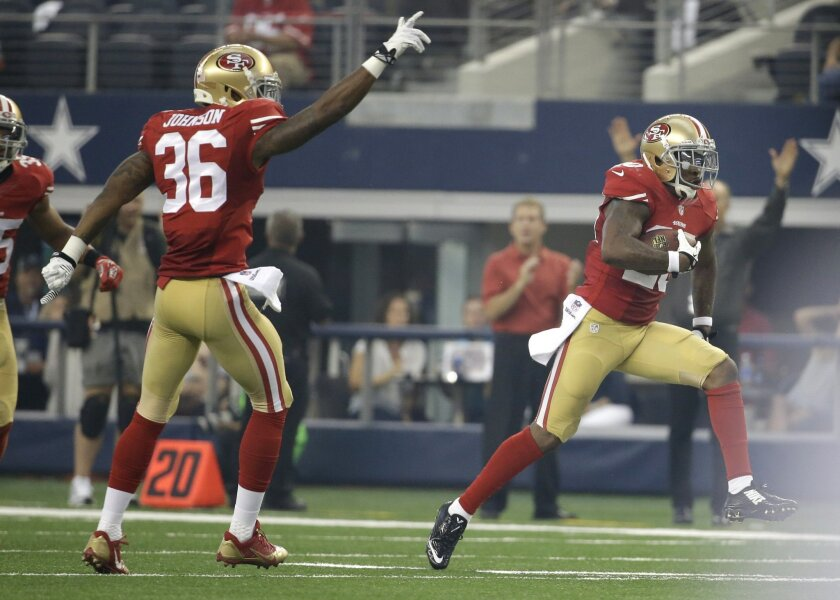 San Francisco Dontae Johnson (36) gestures as teammate defensive back Perrish Cox (20) runs back an interception against the Dallas Cowboys in the first half of an NFL football game, Sunday, Sept. 7, 2014, in Arlington, Texas. (AP Photo/Tony Gutierrez)
