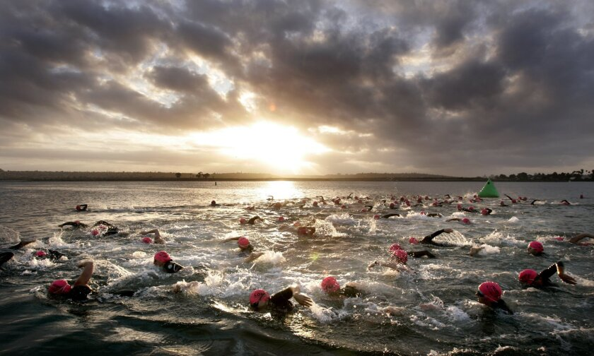 Triathletes started the 500-meter swimming portion of the event at Ski Beach as the sun came up. (Howard Lipin / Union-Tribune)