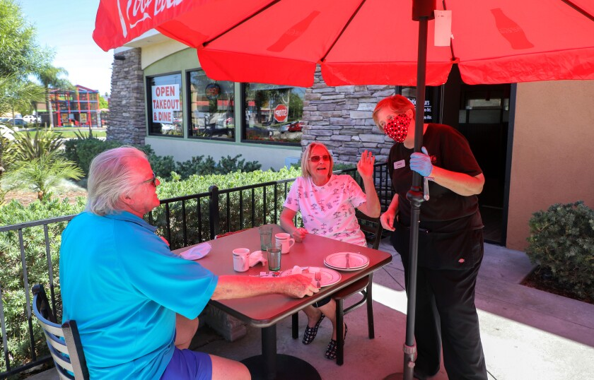Waitress Kimberly Forrest takes care of customers Larry and Connie Clay.