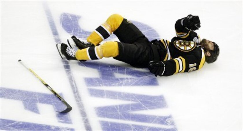 Boston Bruins right wing Nathan Horton lies on the ice after being checked to the ice by Vancouver Canucks' Aaron Rome during the first period in Game 3 of the NHL hockey Stanley Cup Finals in Boston, Monday, June 6, 2011. Rome was called for a 5 minute interference major and a game misconduct. (AP Photo/Charles Krupa)