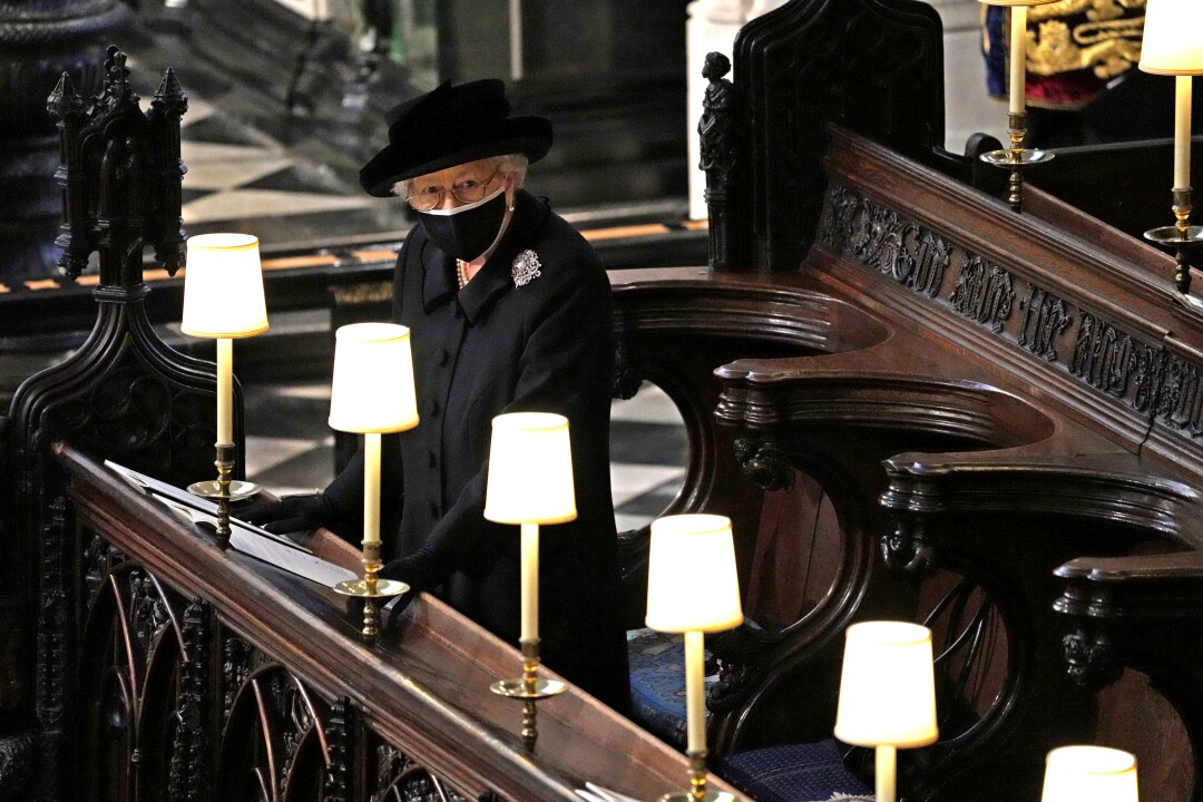 Queen Elizabeth II stands in a pew in St. George's Chapel during the funeral