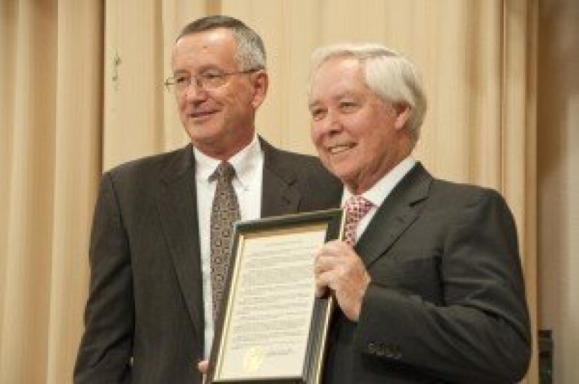 New Mayor Terry Sinnott (left) on Dec. 4 presents Carl Hilliard, the city's outgoing mayor, with a proclamation honoring his longtime service to the city. Photo/Claire Harlin