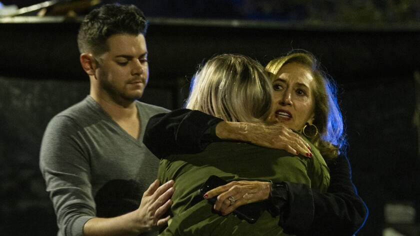 Matthew Rodin and Susan Turner comfort Melissa Hutchinson, who treated some of the victims of the shooting Friday in Tallahassee, Fla.