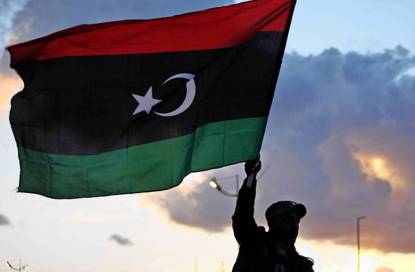 A celebrant in Benghazi, Libya, waves the national flag a commemoration of the second anniversary of the revolution that drove Moammar Kadafi from power. A weak post-Kadafi central government has left a security vacuum in the country's isolated south.