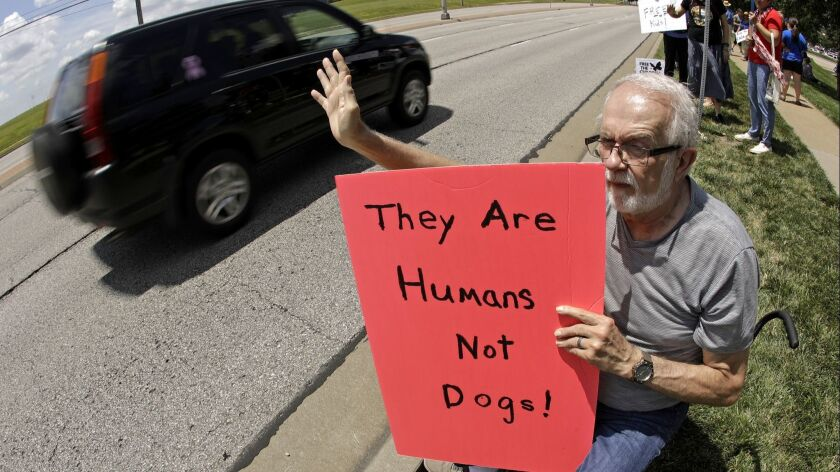 James Trenary, of Overland Park, Kan., holds a sign protesting the treatment of asylum seekers held