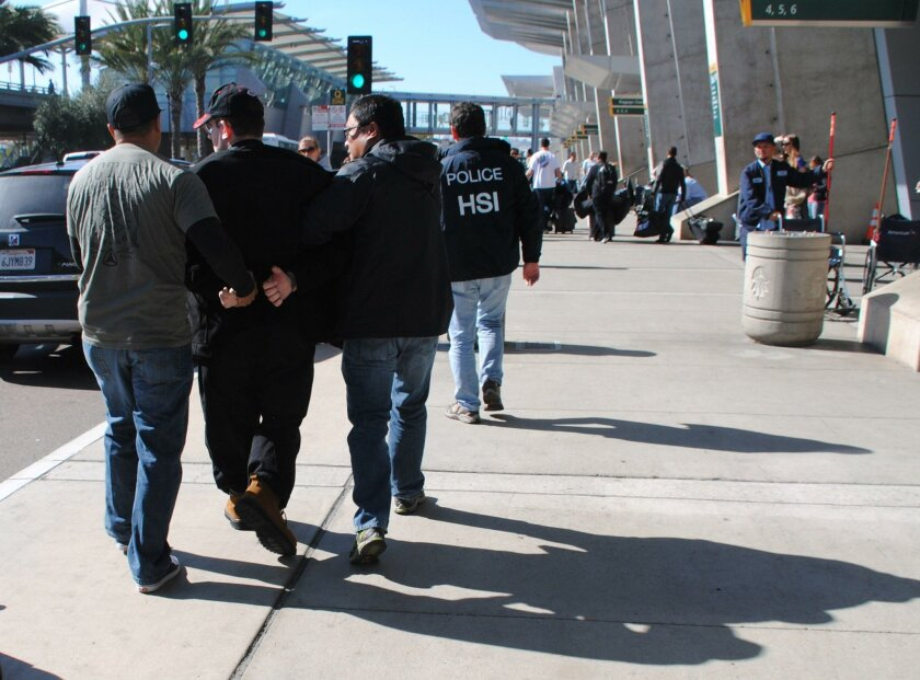 In this Friday, Jan. 29, 2016 photo provided by the U.S. Immigration and Customs Enforcement (ICE), former Columbus, Ohio, seminarian Joel Wright, second left, is arrested at San Diego's airport in San Diego on federal charges for allegedly seeking to have sex with infant and young girls in Mexico.