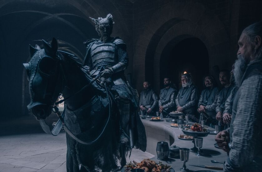 """Ralph Ineson in armor astride a horse in front of a table behind which stand several people in """"The Green Knight."""""""
