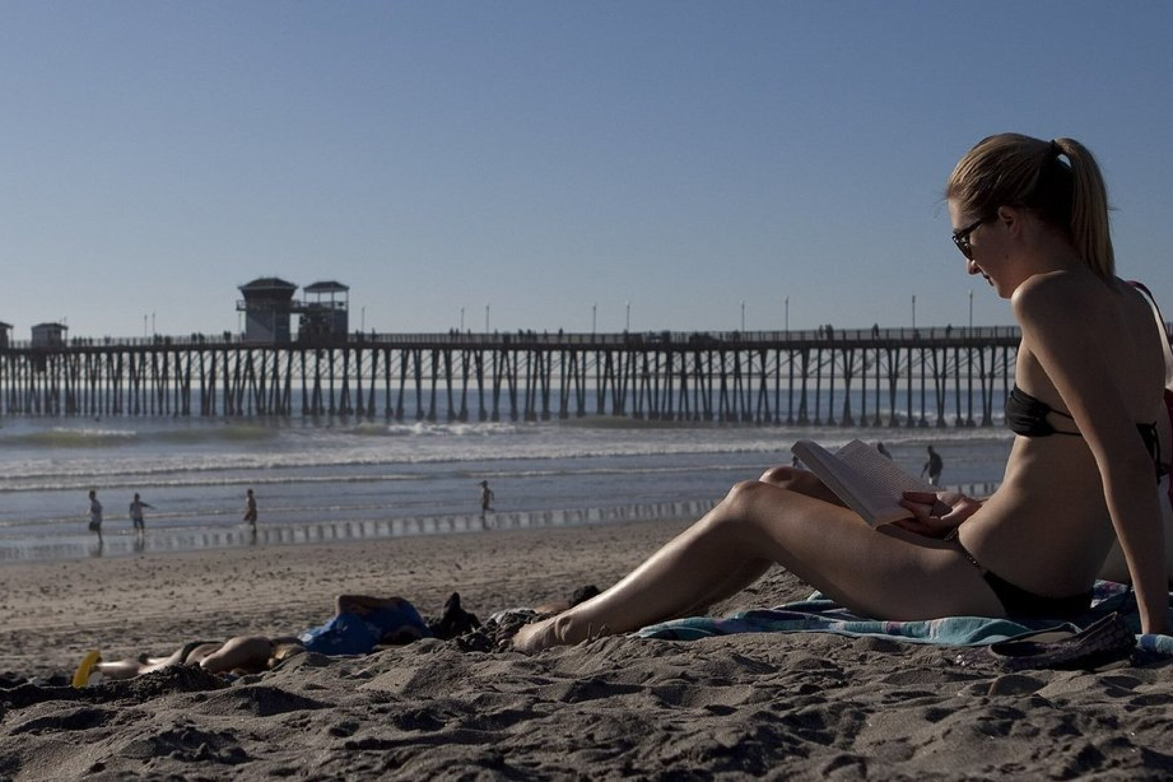 Anna Schultz reads a book on the beach south of Oceanside Pier. The 1,942-foot-long pier is the city's sixth, the fifth at this site.