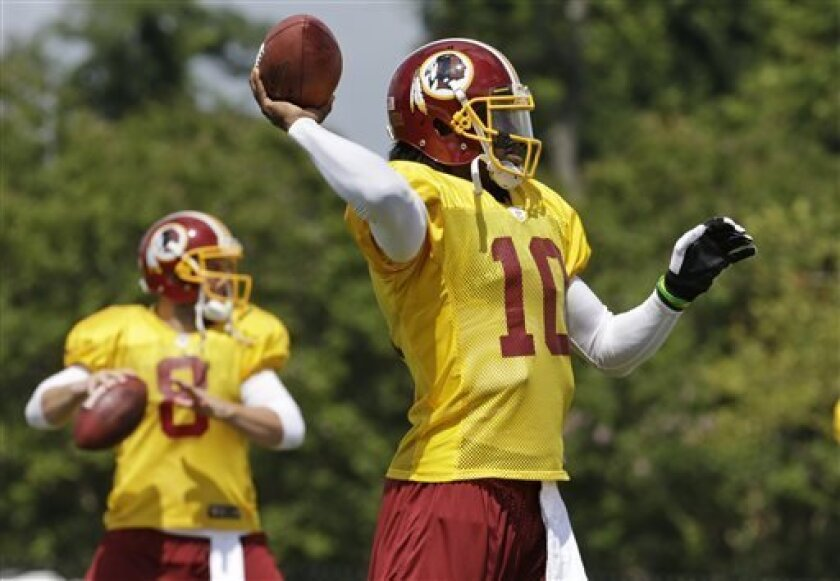 Washington Redskins quarterbacks Robert Griffin III (10) and Rex Grossman (8) look for receivers during the afternoon practice at the NFL football team's training camp in Richmond, Va., Thursday, Aug. 1, 2013. (AP Photo/Steve Helber