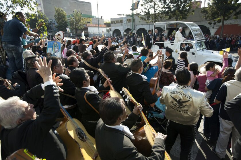 Mexican Mariachis Play and wave to Pope Francis on his route to the Basilica of Guadalupe in Mexico City, Saturday, Feb. 13, 2016. The pontiff's five-day visit includes a prayer before the Virgin of Guadalupe shrine, the largest and most important Marian shrine in the world and one that is particul