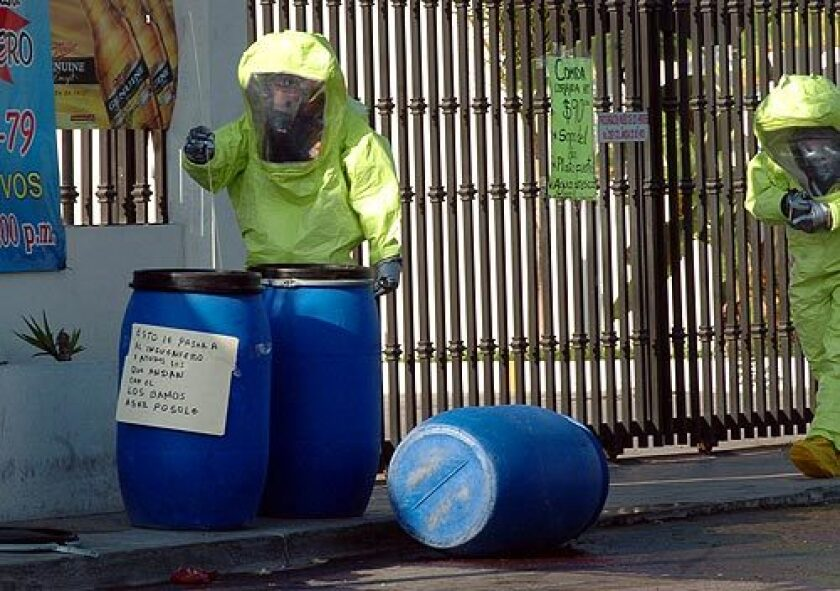 """A forensic investigator inserts a probe into one of three barrels found outside a Tijuana restaurant. The barrels contained human remains dissolved in acid. A handwritten message presumably from """"El Teo"""" warns that all those who walk with a rival drug gang headed by """"The Engineer"""" will be turned into pozole, a stew. More photos >>>"""