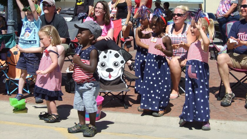 Children dressed in red, white and blue watch the Fourth of July parade in Belle Fourche, S.D.