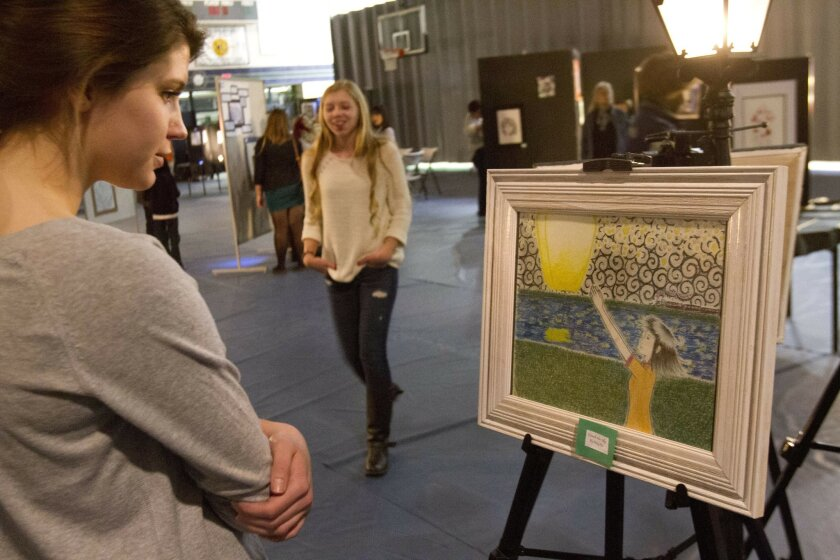 Lindsay Mitchell, 17, left, views an art piece called Touch the Sky by Amy Pai at the third annual Chaparral High School Art Gallery displayed in the gym of the Temecula school Wednesday evening.