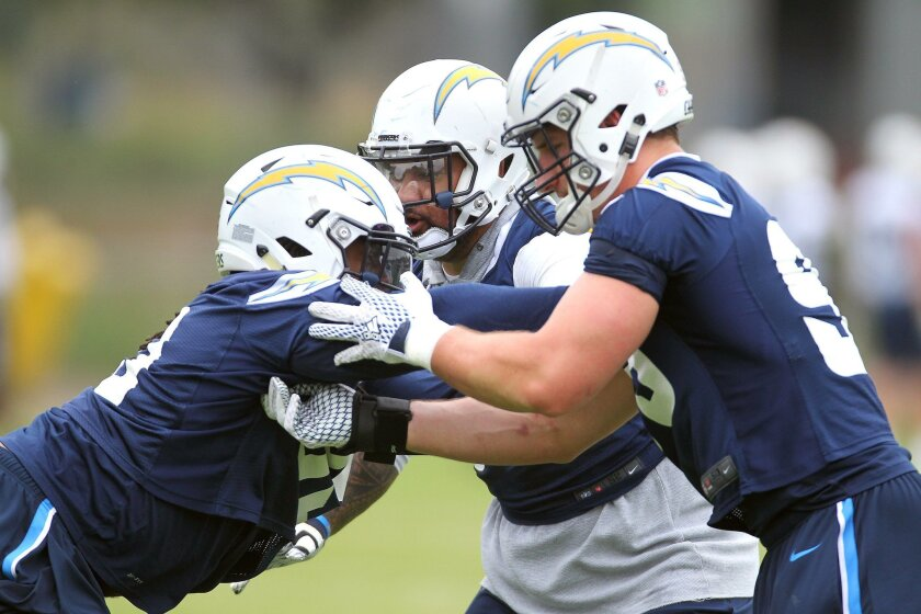 Defensive ends Darius Philon, left, and Joey Bosa go at it during practice.