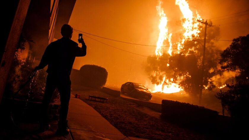 A man hoses down the front of a building and takes a picture of flames getting closer to homes in Ventura.