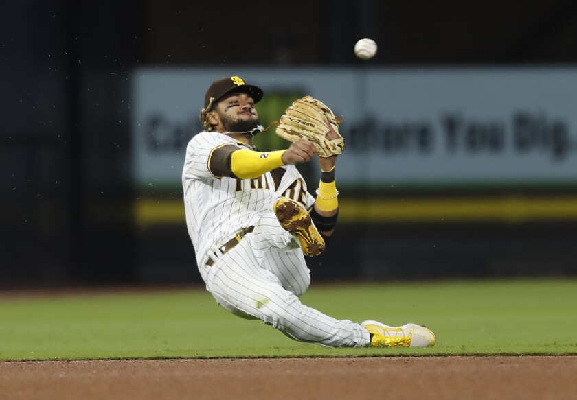 The Padres' Fernando Tatis Jr. tries to throw out the Dodgers' Max Muncy at second base in the fifth inning on Friday.