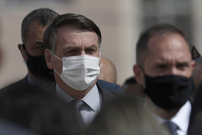 Wearing a mask to curb the spread of the new coronavirus, Brazil's President Jair Bolsonaro arrives for a ceremony to deliver affordable homes built by the government, in a neighborhood of Brasilia, Brazil, Monday, Apr. 5, 2021. (AP Photo/Eraldo Peres)