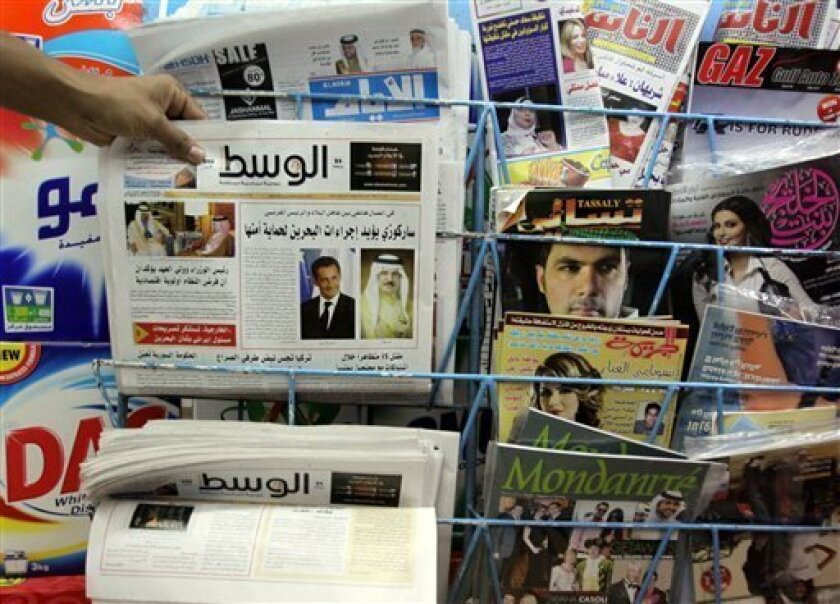 A man picks up a copy of Al Wasat newspaper at a newsstand in Hamad Town, Bahrain, on Tuesday, April 5, 2011. Bahraini authorities on Tuesday deported two journalists working for the opposition's main newspaper, their colleagues said. The government has accused Al Wasat of unethical coverage of the Shiite uprising against the Sunni rulers. (AP Photo/Hasan Jamali)