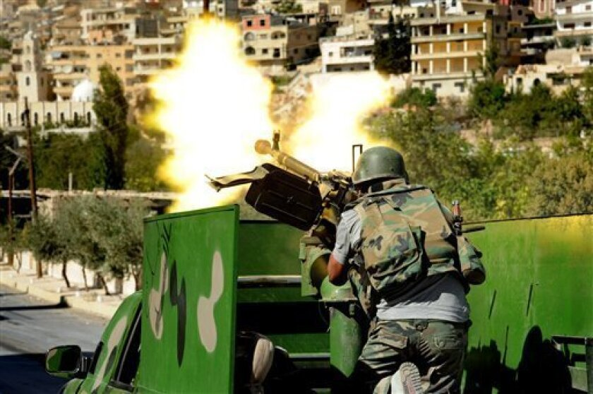 FILE -- In this Saturday, Sept. 7, 2013 file photo released by the Syrian official news agency SANA, a Syrian military solider fires a heavy machine gun during clashes with rebels in Maaloula village, northeast of the capital Damascus, Syria. Syrian troops launched an attack Monday, Sept. 9, 2013, on suspected rebel-held positions on hills overlooking a Christian-majority village near the capital Damascus, two days after rebel forces captured the ancient community, an activist group said. (AP Ph