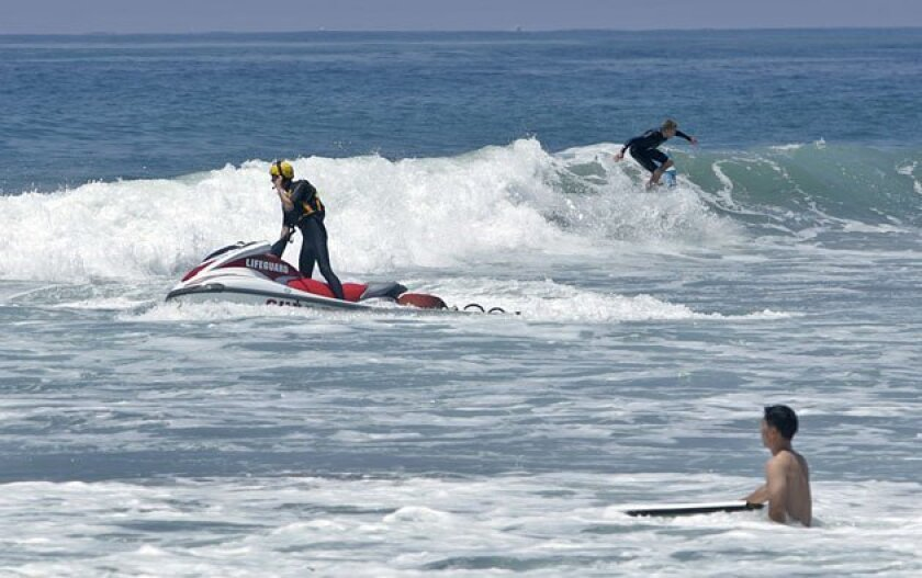 A lifeguard patrolled the waves off Pacific Beach on a personal watercraft during a day of particularly big surf recently. (K.C. Alfred / U-T)