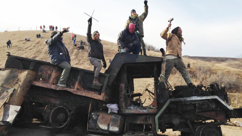 Protesters against the Dakota Access oil pipeline stand on a burned-out truck near Cannon Ball, N.D., on Nov. 21.
