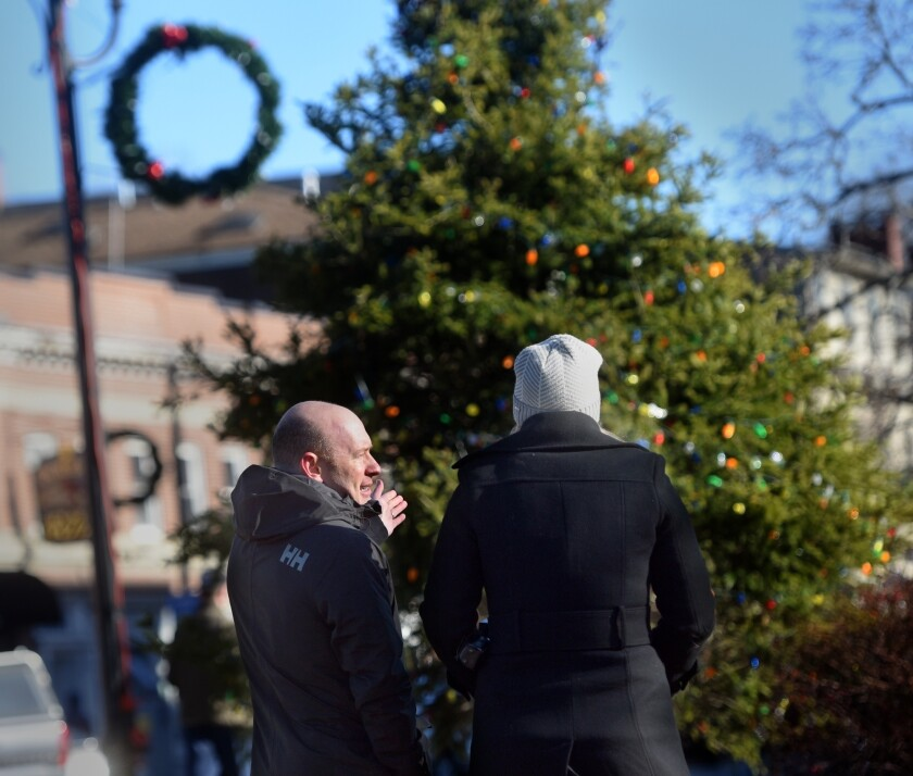 """FILE — In this Dec. 2018 file photo Durham Town Administrator Todd Selig, left, speaks to an unidentified woman in front of a decorated tree on public land, in Durham, N.H. After concerns in 2018 that the tree-lighting ceremony at a park in Durham was too focused on Christmas, and a decision to deny a menorah to be displayed next to the tree, town councilors came up with the idea of a celebration that pays tribute to winter called """"Frost Fest."""" (Deb Cram/Foster's Daily Democrat via AP)"""