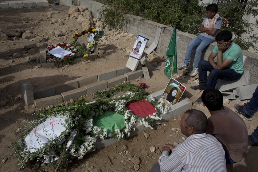 Palestinian mourners visit the grave of Riham Dawabsheh after her funeral in 2015. Her husband and child are buried next to her.