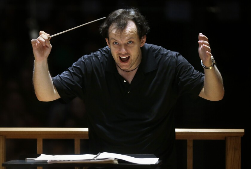FILE — In this Nov. 20, 2014 file photo, Boston Symphony Orchestra music director Andris Nelsons rehearses with the orchestra at Symphony Hall, in Boston. Nelsons has reached agreement on contract extensions with both the Boston Symphony Orchestra and the Gewandhausorchester of Leipzig, Germany, the parties announced on Monday, Oct. 5. With the three-year contract extension, Nelsons is to remain the BSO's music director through the the 2024-25 season. (AP Photo/Steven Senne, File)