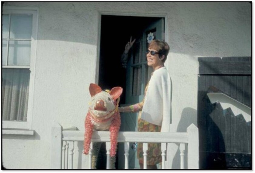 A 1965 photo of Phyllis Gebauer and her friend Thomas Pynchon, seen waving a peace sign from behind the door, in Southern California.