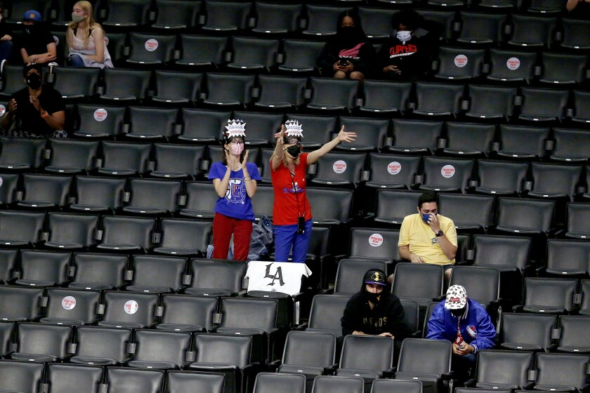 A small cluster of fans in stands surrounded by empty seats