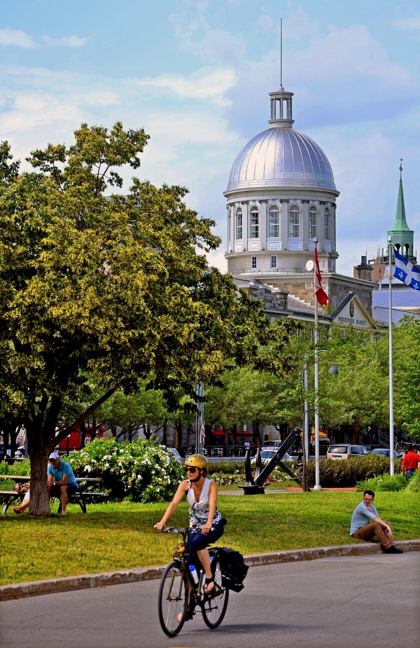 A cyclist rolls through Old Montreal near the dome of the Marché Bonsecours.