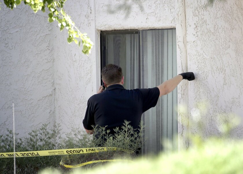 A Phoenix police detective stands outside a home, Thursday, June 2, 2016 in Phoenix where three boys were killed during a several hour period Wednesday night.  The boy's mother was hospitalized in critical condition with self-inflicted stab wounds according to Phoenix police. (AP Photo/Matt York)