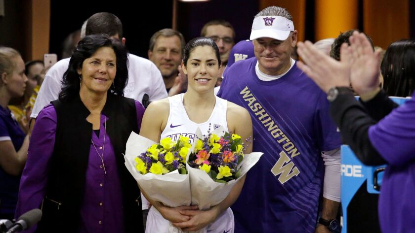 Washington's Kelsey Plum, center, walks onto the court with her parents Katie and Jim Plum for Senior Night after setting the NCAA scoring record.