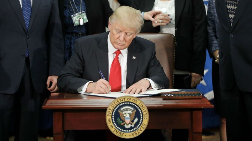 In this Jan. 25, 2017, photo, President Donald Trump signs an executive order for border security an