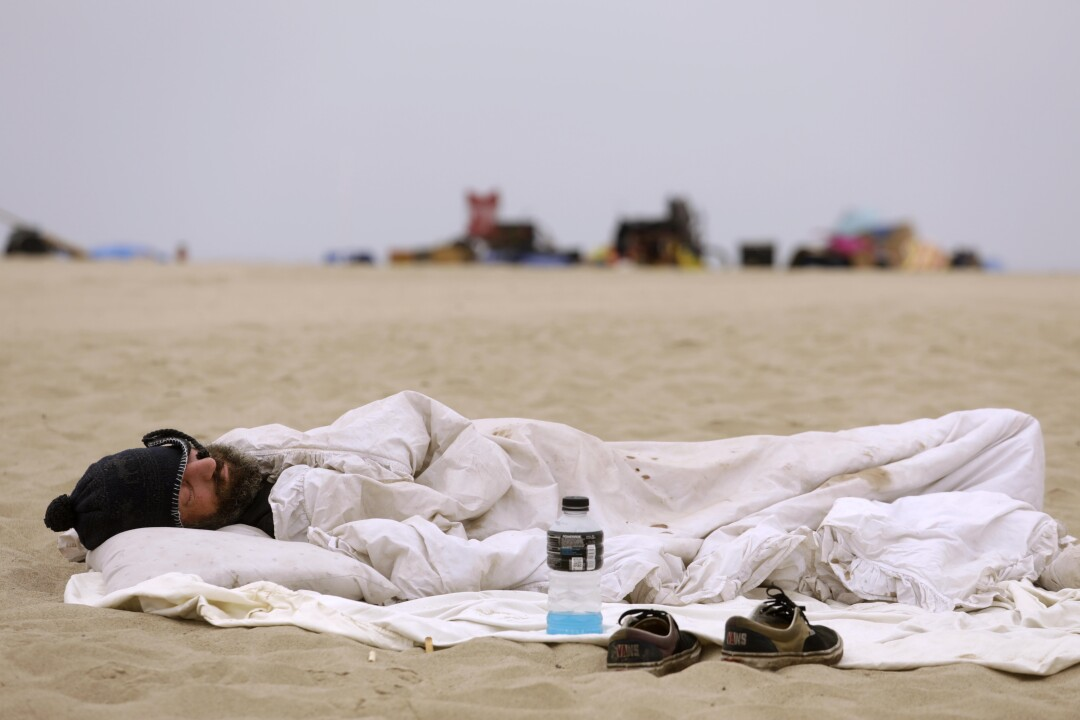 A homeless man sleeps on the beach before City of Los Angeles sanitation workers showed up to clear homeless encampments