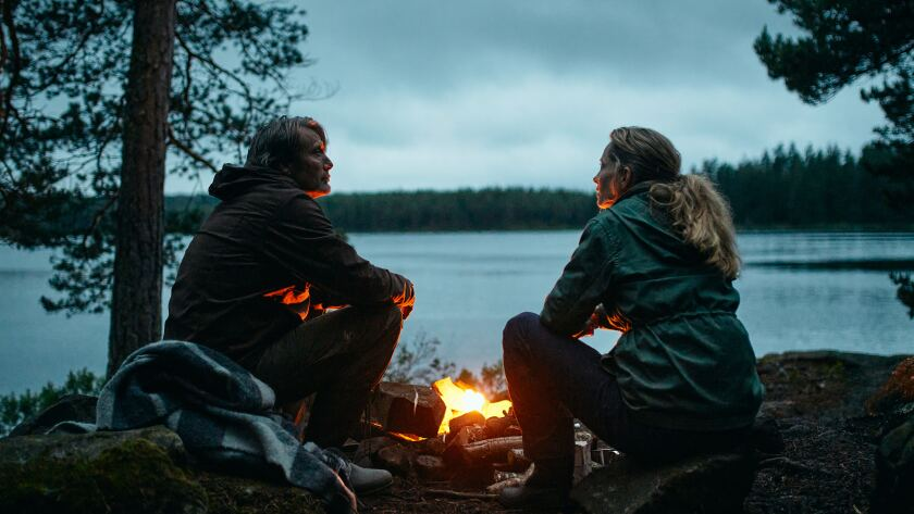 A husband and wife sit by a campfire beside a lake.