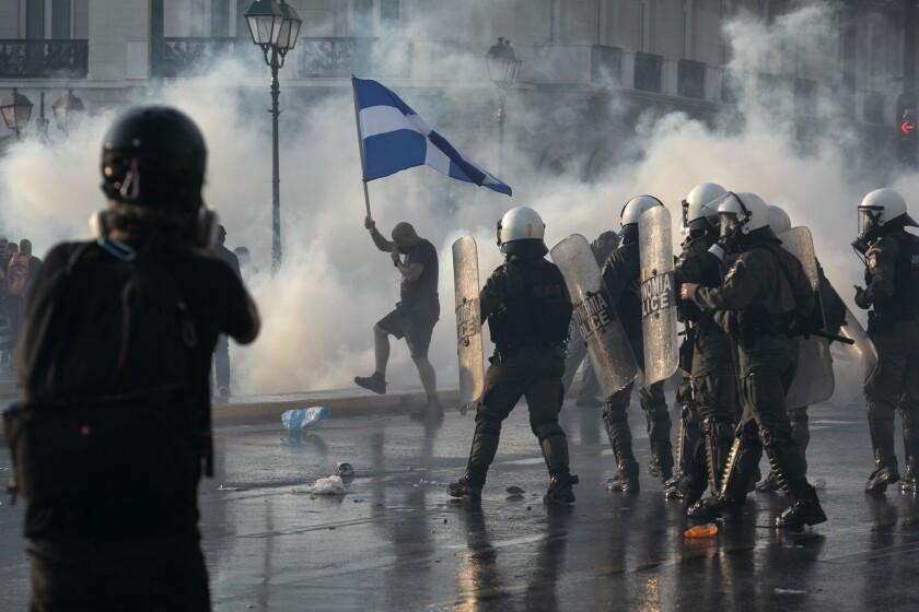 La policía de Grecia usa gas lacrimógeno para dispersar a unos manifestantes durante un mitin en la plaza Sintagma, en el centro de Atenas, el miércoles 21 de julio de 2021. (AP Foto/Yorgos Karahalis)
