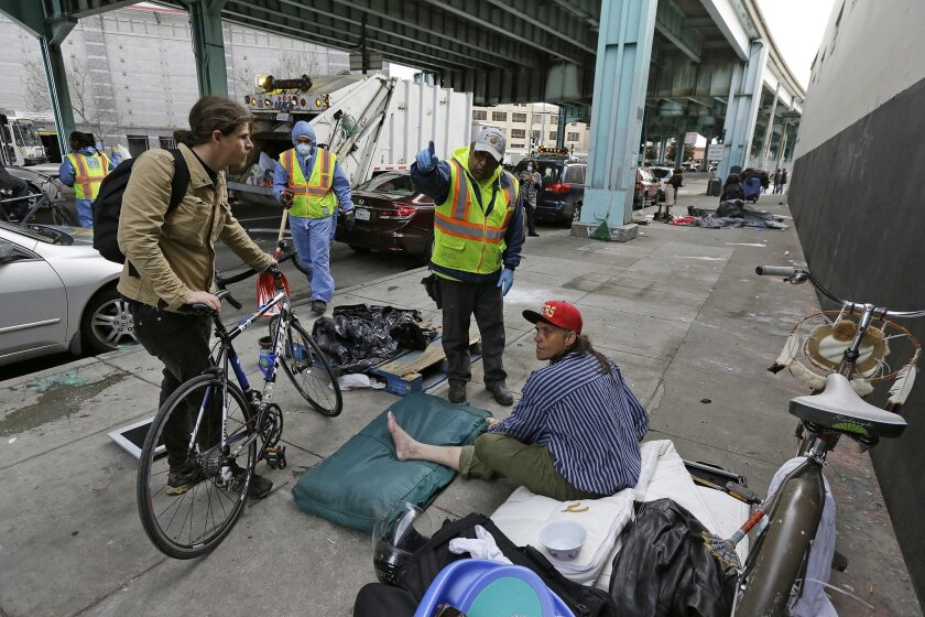 File - In this Feb. 26, 2016, file photo, a city worker tells a homeless man that the area next to him on is about to be power washed and points to an area he might want to move in San Francisco. Media outlets in San Francisco plan to saturate internet, broadcast and print publications this week wi