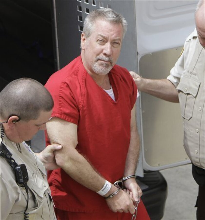 FILE - In this Friday, May 8, 2009 picture, former Bolingbrook, Ill., police sergeant Drew Peterson arrives at the Will County Courthouse in Joliet, Ill. for his arraignment on charges of first-degree murder in the 2004 death of his former wife Kathleen Savio, who was found in an empty bathtub at home. (AP Photo/M. Spencer Green)