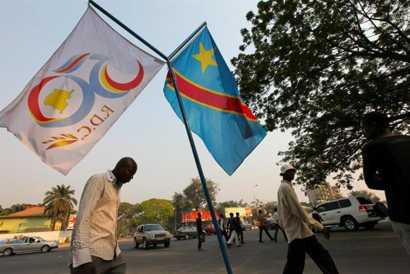 Fotografía distribuida el domingo 27 de junio de 2010, de varios congoleños caminando bajo la bandera nacional y otra que conmemora el 50 aniversario de la independencia de la República Democrática del Congo, ex colonia belga, en Kinshasa, República Democrática del Congo, el 26 de junio de 2010. EFE/Archivo