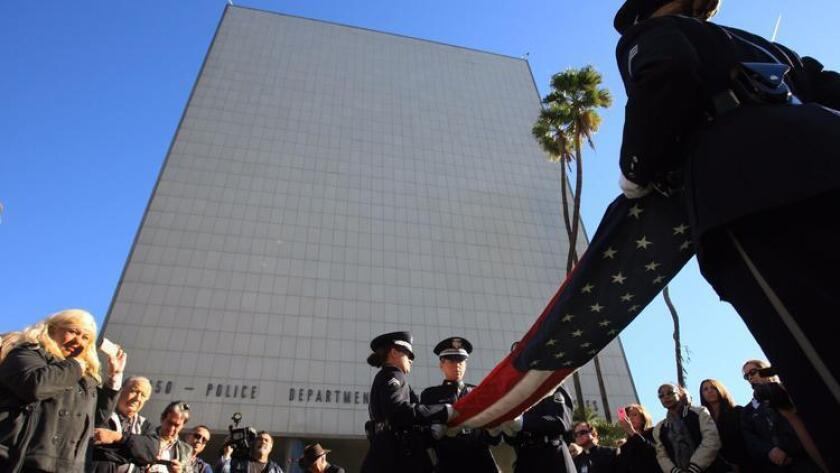An LAPD honor guard folds the American flag after it is taken down from the Parker Center flagpole for the last time during a ceremony on Jan. 15, 2013.
